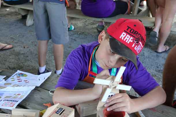 Camper Denver working away on his wood-crafting skills creating a windmill from Home Depot