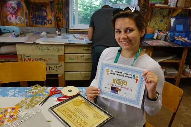 Volunteer companion Janessa showing off her award (in progress) for camper Kaija