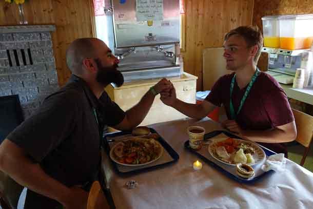 "Volunteer Daniel with camper Braeden enjoying their ""romantic"" candlelit dinner."
