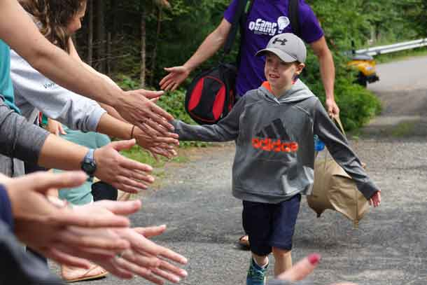 Camper Ryder arriving at camp and making his way down the line of welcome high-fives from our volunteer staff.