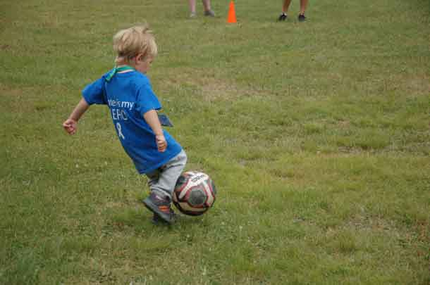 Camper Parker kicking his way into first base at our soccer/baseball game.