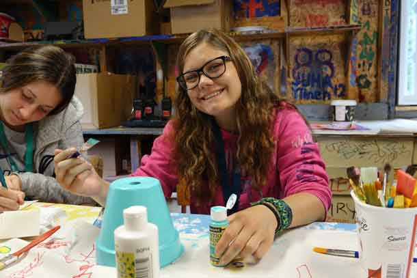 Camper Kaija finishing up her crafts from this week in the craft shack with volunteer Jaqueline.