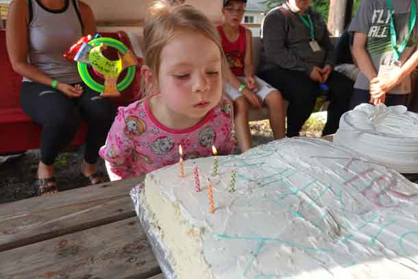 Camper Ally blowing out the candles on the birthday cake made to celebrate her special day.