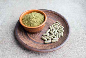 Supplement kratom green capsules and powder on brown plate. Herbal product alt-medicine kratom is opioid. Home alternative pain remedy, opioid addiction, dangerous painkiller, overdose. Image deposit photos.com