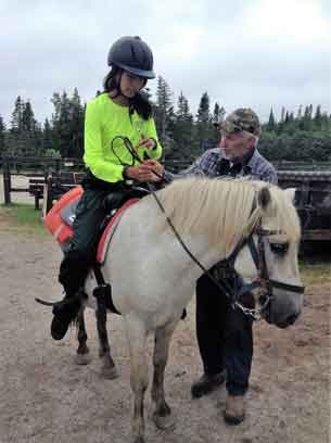 Junior Ranger Chasity Koosees of Kashechewan sits on a horse for the first time.