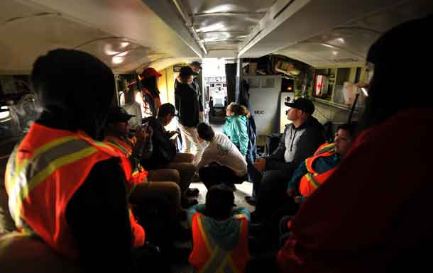 Storytime in the belly of a CL-415 Air Tanker. Stewardship Youth Rangers from the Dryden area listen to Co-Pilot Mike Towill describe his childhood fascination with water bombers and the goals he set in his youth to one day fly them. Photo: AFFES-Chris Marchand
