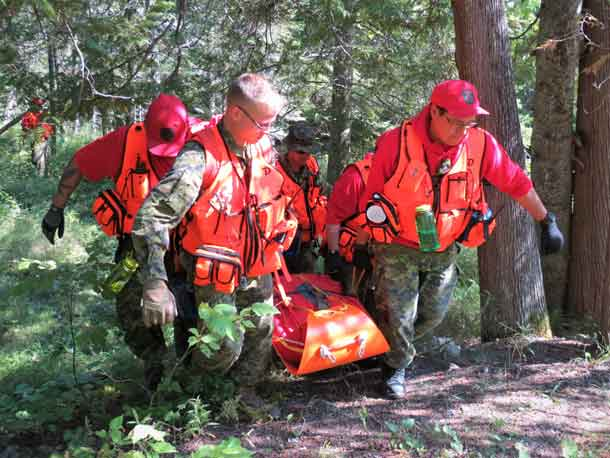 "Canadian Rangers carry a ""victim"" on a stretcher during a search and rescue training exercise."