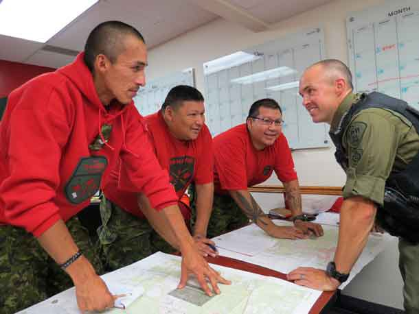 Ontario Provincial Police Constable Curtis Boychuk, right, reviews map reading points with Canadian Rangers during search and rescue training.