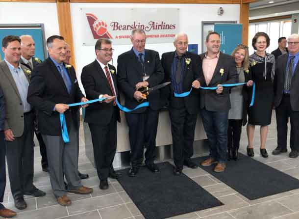 Airport officials, dignitaries and elected leaders help cut the ribbon at the Kenora Airport