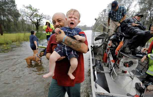 Oliver Kelly, 1 year old, cries as he is carried off the sheriff's airboat during his rescue from rising flood waters in the aftermath of Hurricane Florence in Leland, North Carolina, U.S., September 16, 2018. REUTERS/Jonathan Drake
