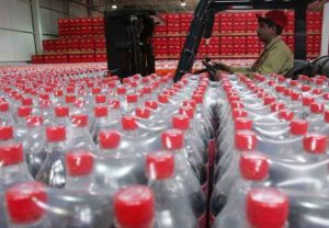 ARCHIVE PHOTO: A worker passes by bottles of Coca-Cola at the newly inaugurated bottling plant in Kabul, Afghanistan September 10, 2006. REUTERS/Ahmad Masood
