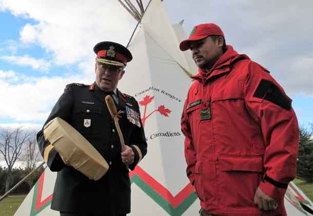 Brigadier-General Jocelyn Paul uses Ranger Howard Jacob's drum to sing a song from his boyhood while growing up on the Huron-Wendat First Nation. Photo by Sgt Peter Moon