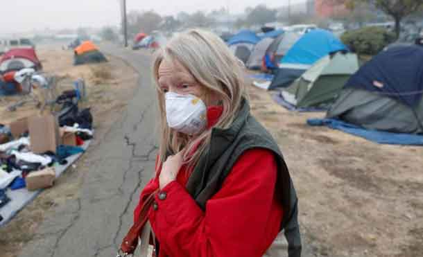 Bridgett Hogan, 57, of Paradise, walks through a makeshift evacuation center for people displaced by the Camp Fire in Chico, California, U.S., November 15, 2018. REUTERS/Terray Sylvester