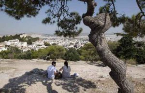 Archive Photo: Tourists sit under a pine tree on a hill overlooking Athens July 7, 2011. REUTERS/John Kolesidis