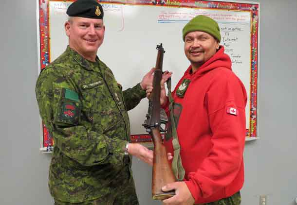 Lieutenant-Colonel Matthew Richardson,left, presents one of the old Ranger .303 rifles as a gift to Sergeant Neil Neegan of the Constance Lake Ranger patrol.