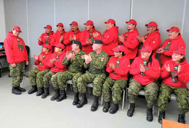 Canadian Rangers waiting for a training class photograph to be taken applaud Sergeant Linda Kamenawatamin, left, on learning she is to receive the Order of Military Merit.
