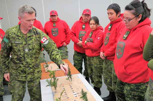 Warrant Officer Christopher Thomson uses an improvised model to show Canadian Rangers how to make an emergency aircraft landing strip.