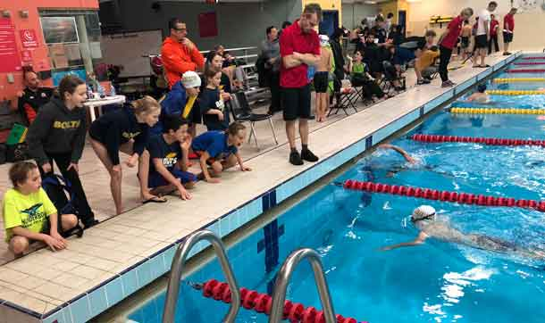 Fenn Dobson swimming with his Thunderbolt team mates cheering him on.