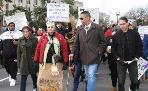 """Mashpee Wampanoag Tribal Council Chairman Cedric Cromwell and Mashpee Wampanoag Tribal Council Vice-Chair Jessie """"Little Doe"""" Baird walk during a November 14 rally in Washington, D.C., USA. Handout photo by Sean Gonsalves"""