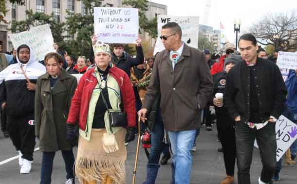 "Mashpee Wampanoag Tribal Council Chairman Cedric Cromwell and Mashpee Wampanoag Tribal Council Vice-Chair Jessie ""Little Doe"" Baird walk during a November 14 rally in Washington, D.C., USA. Handout photo by Sean Gonsalves"