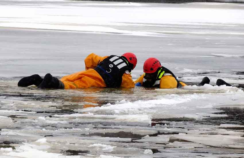 "A rescuer, left, reaches a soldier ""victim."" - image: Sgt Peter Moon"