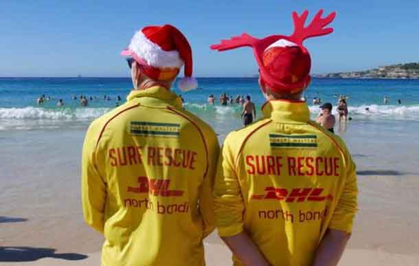 Simon (L) and Victor (R), volunteer life guards from North Bondi Surf Life Saving Club, keep an eye on swimmers enjoying Christmas day on Bondi Beach, Sydney, Australia, December 25, 2018. REUTERS/Jill Gralow