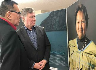 Minister Feehan (right) and Adam North Peigan view Bi-Giwen:Coming Home- Truth Telling From the Sixties Scoop exhibit