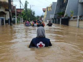 A volunteer wades through floods at a residential area in Makassar, South Sulawesi, Indonesia, January 23, 2019 in this photo taken by Antara Foto. Picture taken January 23, 2019. Antara Foto/Sahrul Manda Tikupadang/ via REUTERS