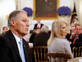 Washington State Governor Jay Inslee (L) listens to participants as U.S. President Donald Trump holds a discussion about school shootings with state governors from around the country at the White House in Washington, U.S,. February 26, 2018. REUTERS/Jonathan Ernst