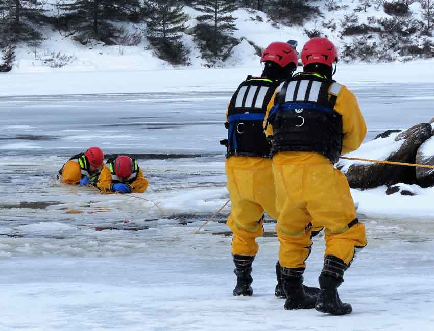 Soldiers haul a victim and his rescuer from broken ice - image: Sgt Peter Moon