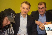 Cat Lake Chief Matthew Keewaykapow signs agreement as Minister O'Regan and Bob Nault watch