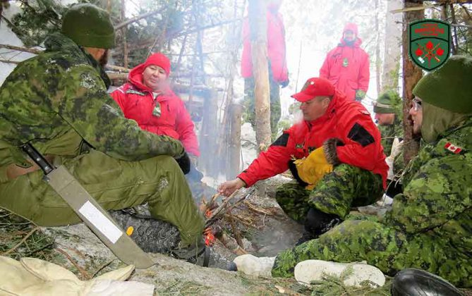 Master Corporals Yvonne Sutherland and Joe Lazarus discuss winter survival skills with two combat engineers. Photo by Sgt Peter Moon