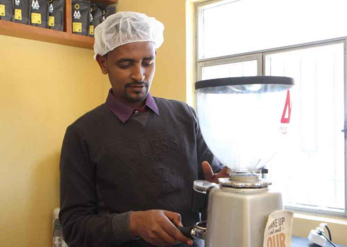 An Ethiopian staff at Moyee's coffee roastery makes coffee with beans that have been roasted and packaged in Ethiopia, in Addis Ababa, Ethiopia, on January 16, 2018. Thomson Reuters Foundation/ Thin Lei Win