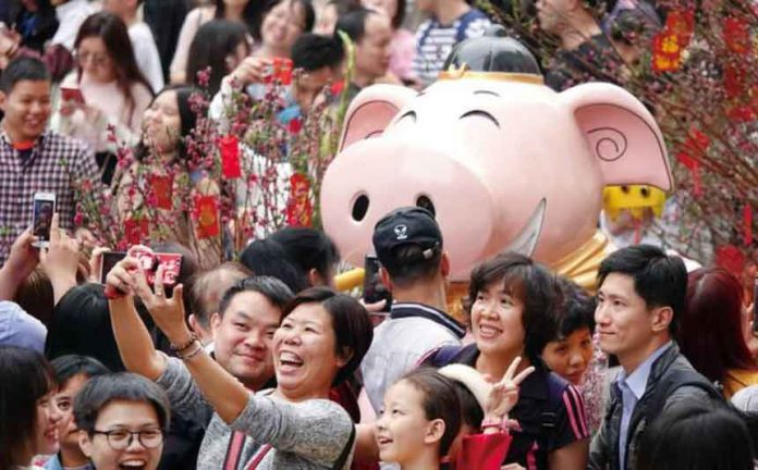 Visitors take pictures of an installation at a flower fair ahead of the Chinese Lunar New Year of the Pig, in Guangzhou, Guangdong province, China February 3, 2019. Picture taken February 3, 2019. REUTERS/Stringer