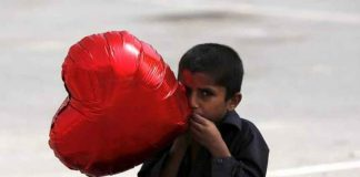 A boy inflates a heart-shaped balloon to sell on Valentine's Day in Karachi, Pakistan February 14, 2016. REUTERS/Akhtar Soomro