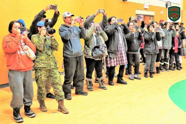 Relatives and friends take pictures during the graduation parade for new Canadian Rangers in Pikangikum.