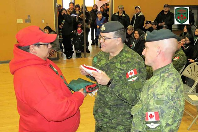 Sergeant Buster Kurahara, left, newly appointed commander of the Pikangikum Canadian Ranger patrol, receives a Ranger flag from Brigadier-General Jocelyn Paul.