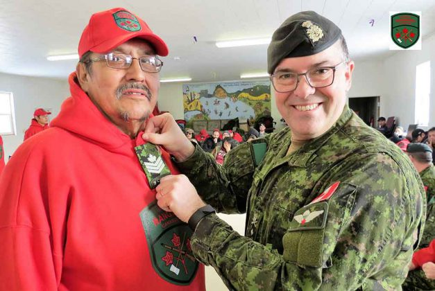 Newly appointed Sergeant Charles Wesley receives his rank insignia from Brigadier-General Jocelyn Paul in Cat Lake.