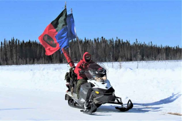 Ranger Quinton Anishinabie leads a territorial surveillance patrol while flying Canadian Ranger and Sandy Lake First Nation flags on his snowmobile.