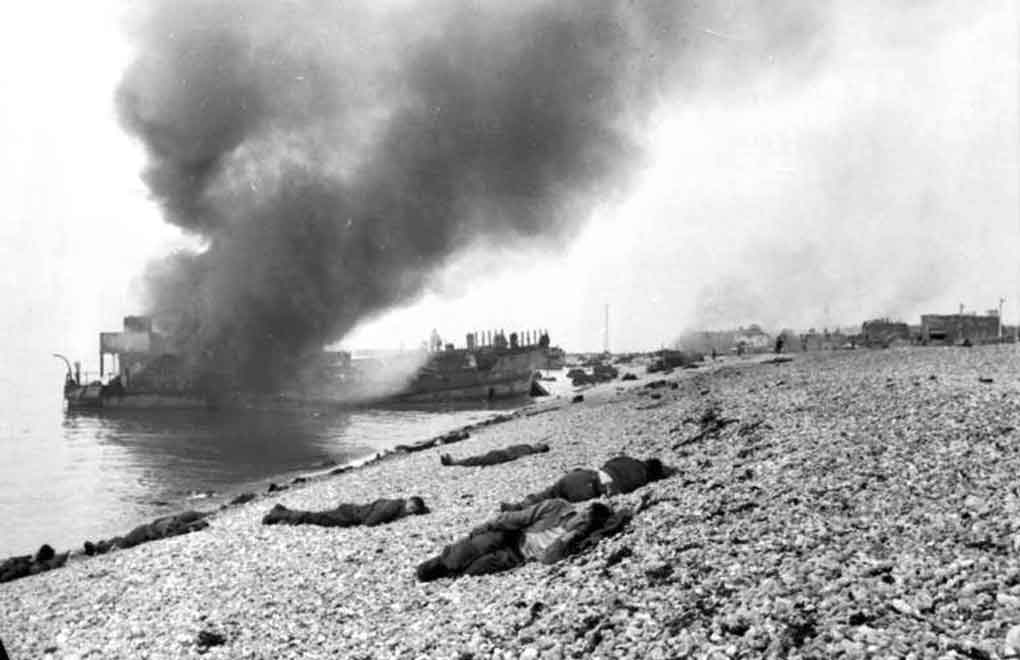More details Destroyed landing craft on fire with Canadian dead on the beach. A concrete gun emplacement on the right covers the whole beach. The steep gradient can clearly be judged.