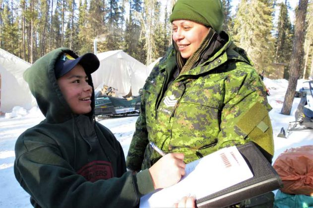 Junior Canadian Ranger Jayvan Ross of Muskat Dam signs an attendance sheet for Sergeant Eva Clarke, an army instructor.