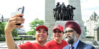 Corporal Angus Sutherland, left, and Master Corporal Paula Nakogee, centre, get a selfie with National Defence Minister Harjit Sajjan in front of the National War Memorial in Ottawa.