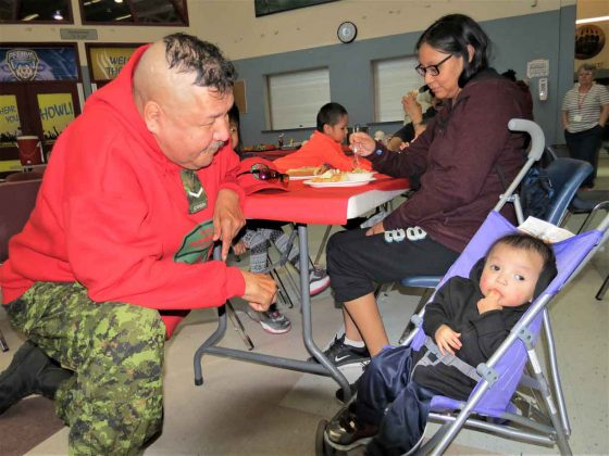 Ranger Rodney Rate plays with one-year-old Landon Quill at Pelican Falls First Nations School.