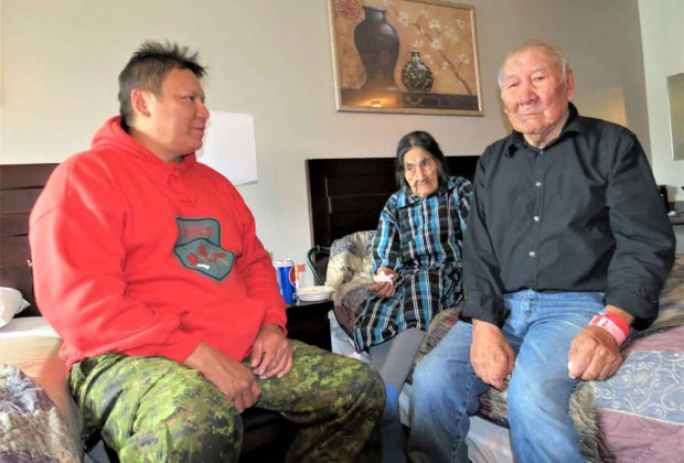 Ranger Bennett Quill, left, speaks in Ojibwa with Pikangikum evacuees and elders Aipi King and her husband, John George King, in a hotel room in Sioux Lookout. The Kings are both 86