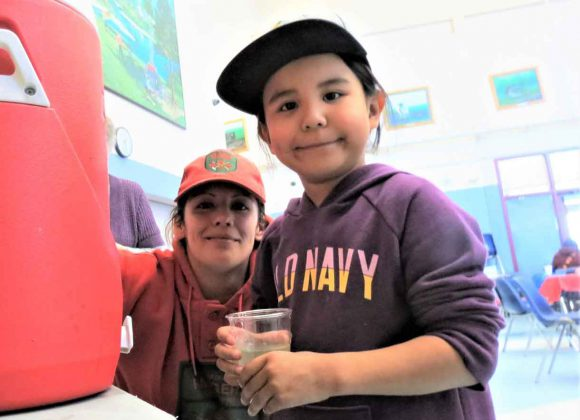 Ranger Carla Slobozian helps Pikangikum evacuee Patience Turtle, five, to get a drink at Pelican Falls First Nations School, near Sioux Lookout