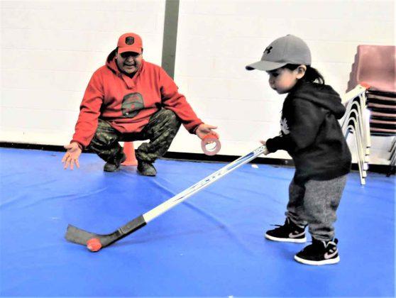 Ranger Freeman Ningewance plays with Pikangikum evacuee Manny Turtle, two, at Pelican Falls First Nation School