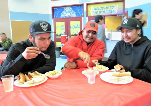 Ranger Freeman Ningewance, centre, talks with Pikangikum evacuees Adrian and Abraham Quill, who are brothers, at Pelican Falls First Nations School.