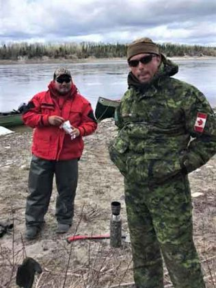 Ranger Malachi Wynne of Kashechewan, left, and Warrant Officer Carl Wolfe take a break on the Albany River.