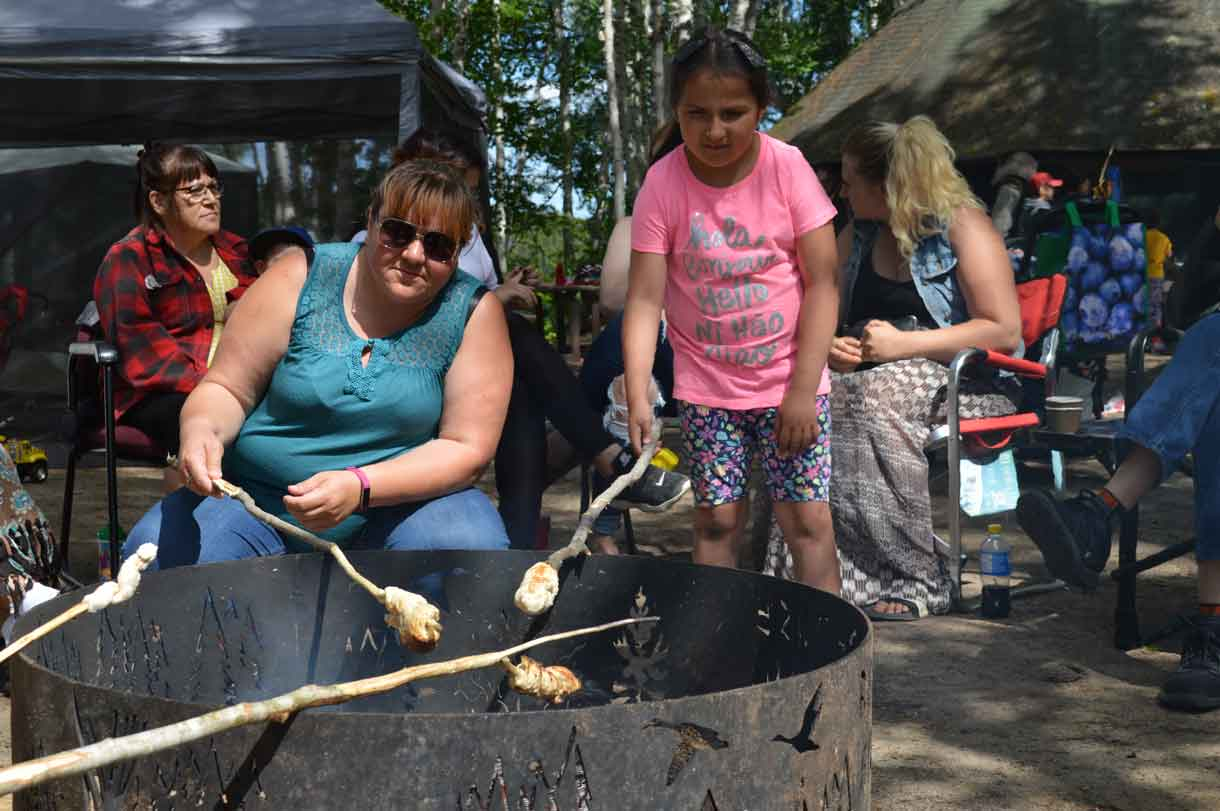 Traditional activities included making bannock at the Indigenous Language Gathering at Dorothy Lake on July 6 and 7. Here we see Amanda Julien, Matachewan FN showing Payton Batisse how to roast bannock over a fire.