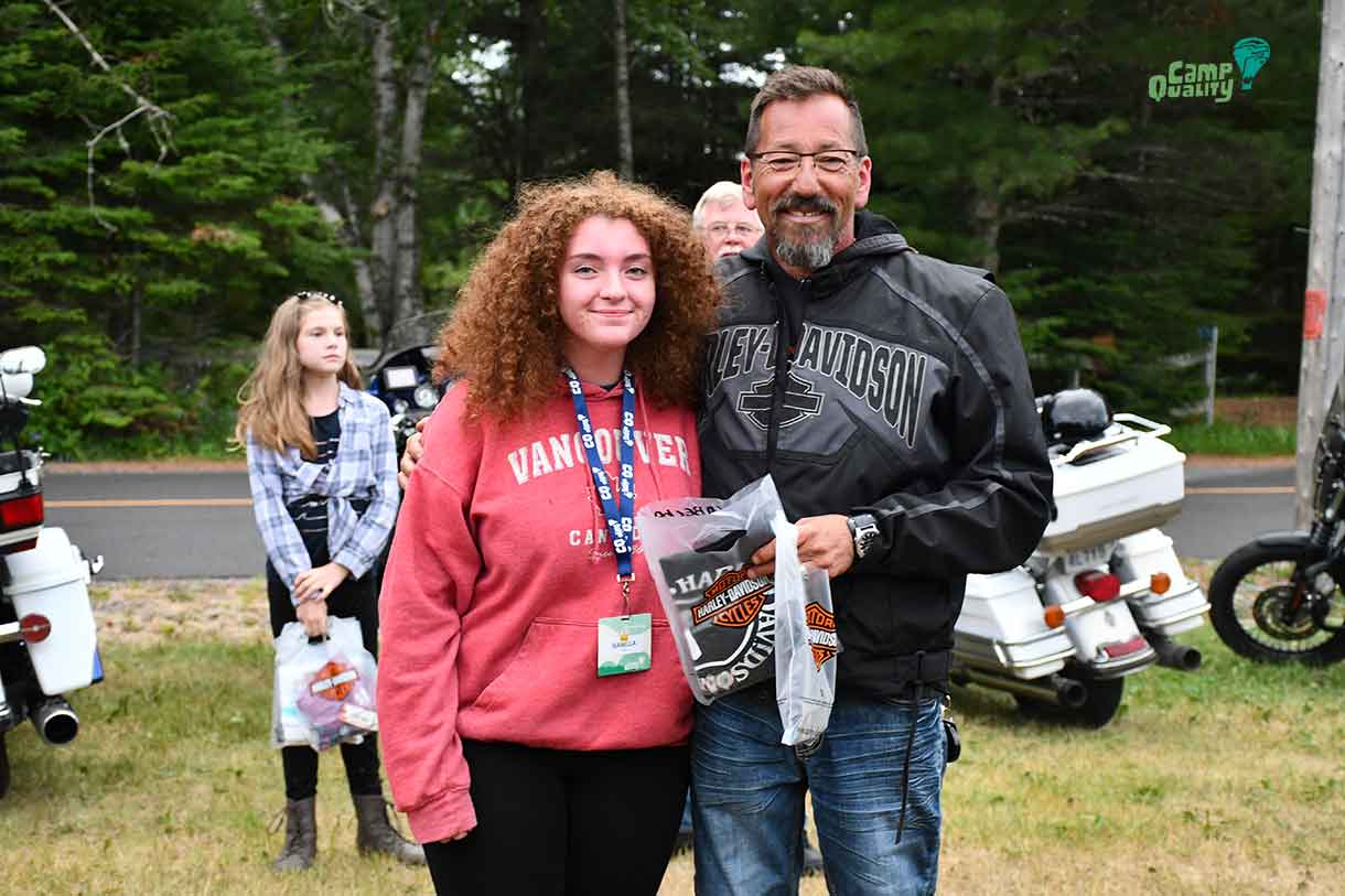 Camper Isabella posing with biker Trent after receiving her Harley Davidson t-shirt.